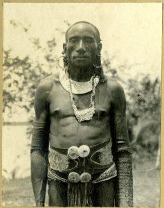 Fig.4 : Photographie (noir et blanc), d'un album ; portrait d'un homme en extérieur portant une ceinture d'écorce avec attaches de coquillages, collier de coquillages, boucles d'oreilles et ornements de bras : Papouasie-Nouvelle-Guinée. Epreuve à la gélatine argentique. Oc,A12.268, AN414768001 © The Trustees of the British Museum